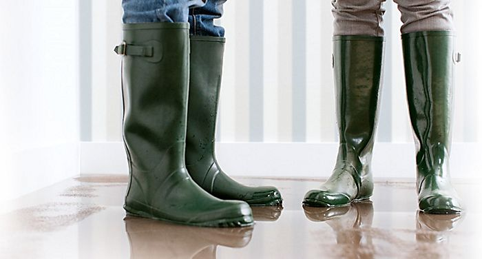 """wellington-booted feet standing indoors on wet flooring"""