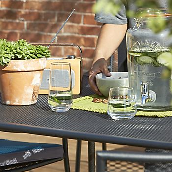 Garden dining table with Kilner drinking dispenser and potted succulent plant