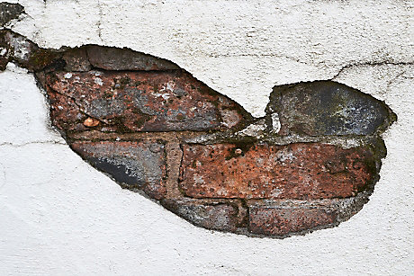 picture of cracked render on brick wall