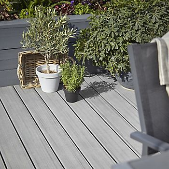 Grey decking combined with grey painted wall and grey plant pots