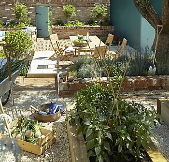 Roscana dining set on patio next to vegetable growing zone in garden