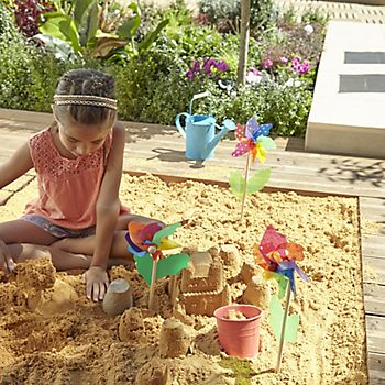 Child playing in a sandpit set into a deck