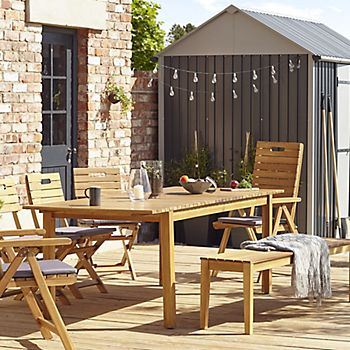 Garden party lights dangling from Indus metal shed behind Denia wooden garden dining set