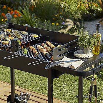 Kebabs and other food cooking on a charcoal barbecue
