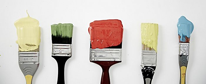 """paint brushes dipped in coloured paints"""