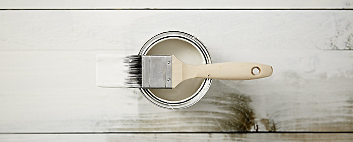 """A selection of grey paint in tins and some paint brushes"""