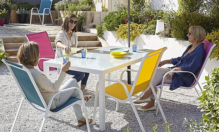 """Friends relaxing with drinks on the Janeiro dining set"""