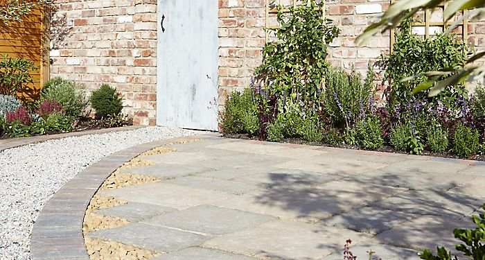 """Grey paving slabs laid next to gravel path in garden"""