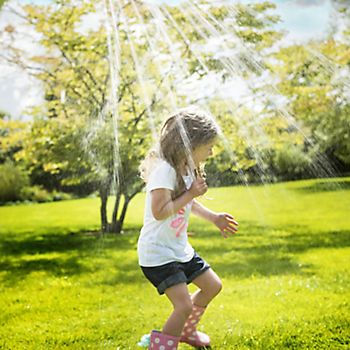 Little girl playing under water sprinkler