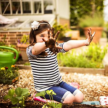 Girl with soil on her hands in garden