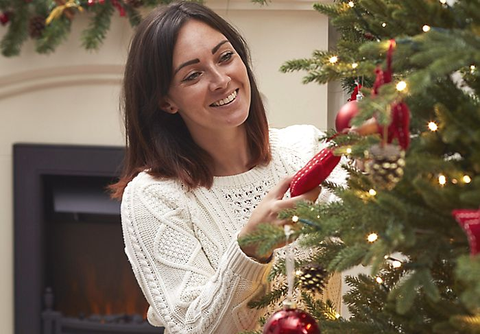 """Woman hanging decorations on a Christmas tree"""