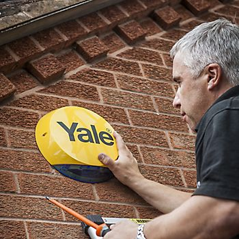 man fitting burglar alarm to the outside of a house