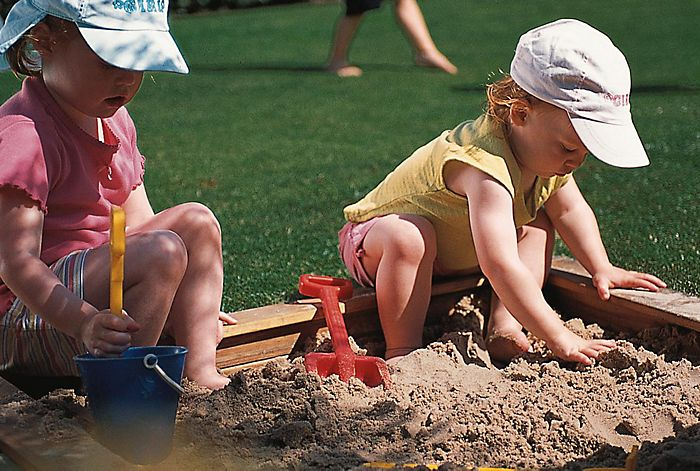 """boy and girl playing in a sandpit"""