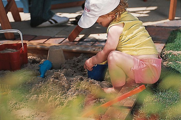 """little girl playing in a sandpit"""